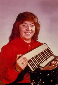 Margaret, older now, holding an accordian. Color portrait.