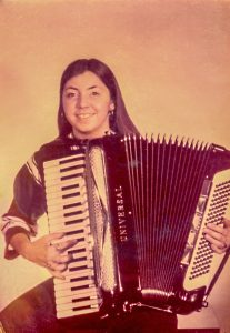 Young Margaret smiling and holding an accordion. Sepia-tone photograph.